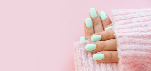 Fotobehang Manicure Tender hands with perfect blue manicure on trendy pastel pink background. Place for tex