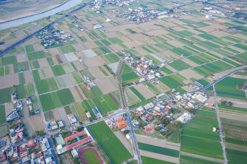 Fields with various types of agriculture and villages beside with air pollution in winter morning, Tainan, Taiwan, aerial view