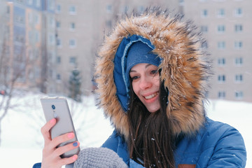Young beautiful woman talking on video on the mobile phone in winter. Face close-up.