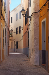 an empty picturesque narrow alley of old painted houses and street lamps in ciutadella menorca