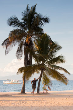 Boy in the shade of palm trees in front of Lake Malawi, Malawi