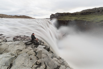 Man sitting on the cliff edge next to Dettifoss waterfall in Vatnayokull national park, Iceland
