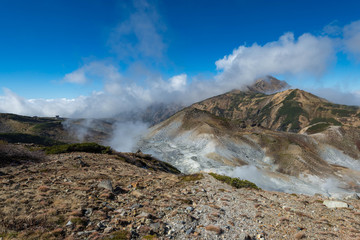 Volcanic vents with smoke and mountains with blue sky, sulphur and ash. Murodo, Japan alps
