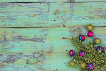 Blank mint green wood sign with Christmas ornaments and garland border; holiday background with copy space