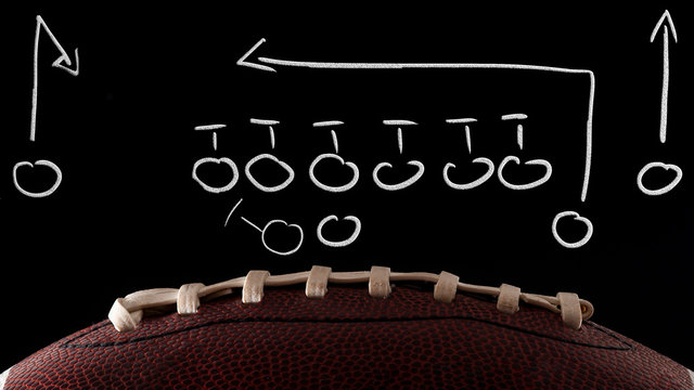 American football tactics scheme, sports coaching and offensive play concept with a ball in front of a blackboard with a game plan drawing done by the coach with dramatic lights