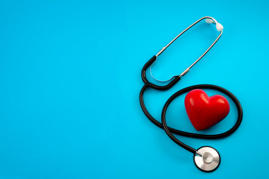 Yearly health check up, disease diagnosis medicine, healthcare and cardiology concept with a red heart and a stethoscope isolated on a hospital blue background with copy space