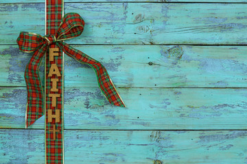 Blank rustic antique teal blue wood sign with red and green plaid Christmas bow border and the word FAITH; holiday background with aged painted copy space