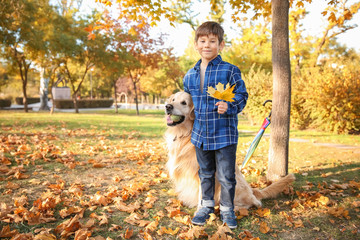 Cute boy with dog in autumn park