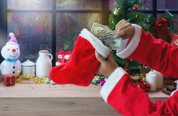 Santa Claus hand hold dollar banknotes with Santa sock against Christmas Decoration background