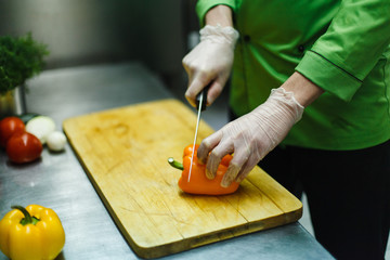cook in gloves cuts vegetables on a wooden board. professional kitchen with steel worktop