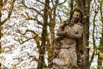 Statue religieuse sans mains couverte de mousse d'un cimetière en Moselle