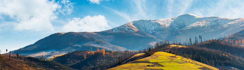 panorama of mountain ridge with snowy peak above the hill with grassy rural fields. wonderful weather condition of november