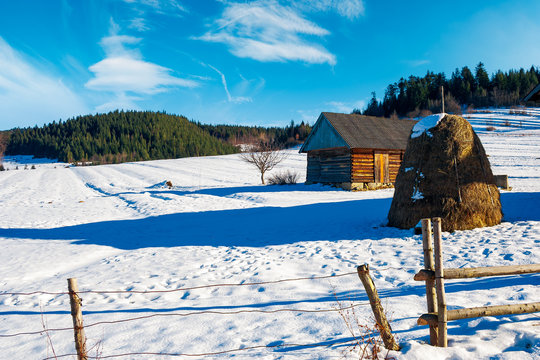abandoned barn in Carpathian mountains. beautiful sunny winter weather. haystack nearby