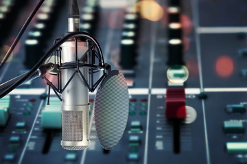 Condencer microphone with pop filter in recording studio..Close up of microphone  setting on stand in front of audio mixing board with colorful light bokeh ,showbiz concept.