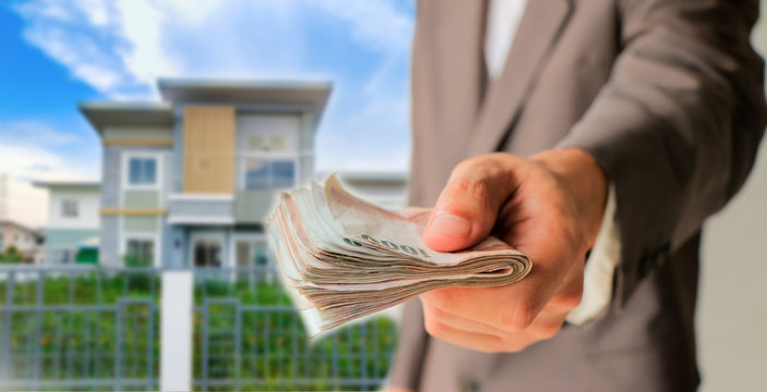 Businessman giving money with blurred home