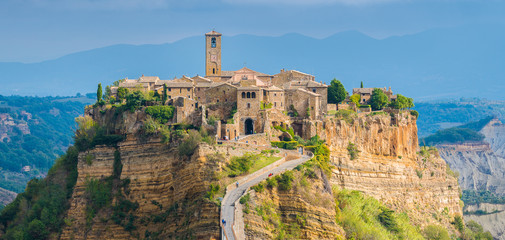 The famous Civita di Bagnoregio hit by the sun on a stormy day. Province of Viterbo, Lazio, Italy. Wall mural