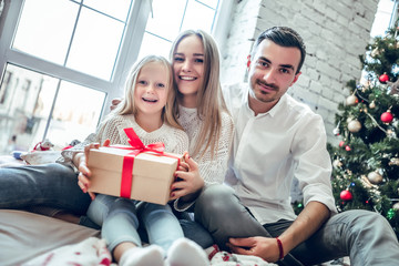 Merry Christmas and Happy Holidays! Family gather around a Christmas tree, holding a present