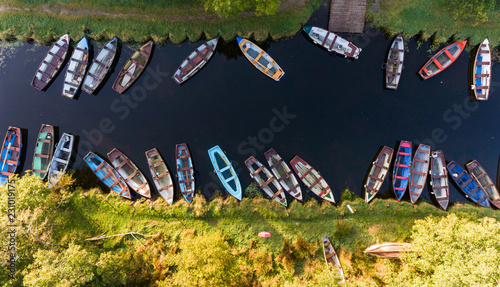 aerial view of small fishing boats in a row on a river canal