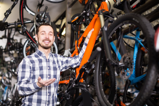 positive man in bicycle shop chooses for himself sports bike