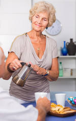 Smiling elderly woman pouring coffee