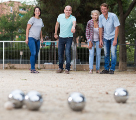 friendly mature couples playing petanque at leisure