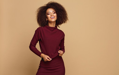 Wall Mural - Beautiful african american model with copy space looking at camera and touching her sweater