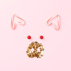 Christmas pig concept made of candy cane lollipops and golden confetti on pink background.