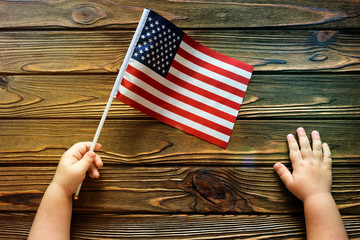 The hand of a child holds an American flag on a wooden background. patriotism. National holiday.