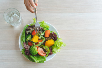 Top view of person eating colorful salad on the table.