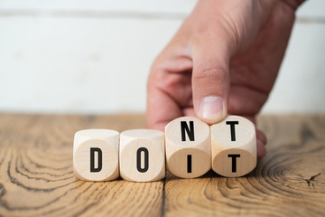 "Hand turns two cubes, changing the word ""don't"" to ""do it"""