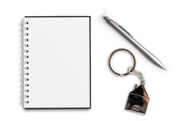 Schreibblock, Stift und Schlüsselanhänger in Hausform auf weißem Hintergrund