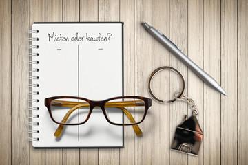 """Checkliste mit Pro und Kontra zum Thema """"Mieten oder kaufen?"""" auf Holzuntergrund"""