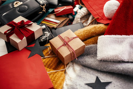 Christmas shopping and seasonal sale. Gift box, credit cards, money, wallet, bags, clothes, jewelry, santa hat, scarf on rustic wood. Space for text. Advertising concept. black friday