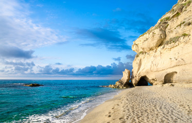 Rock with greenery near sandy beach of Tyrrhenian Sea, Tropea, Italy