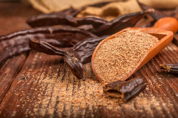 Carob pods and carob powder in a spoon on rustic background