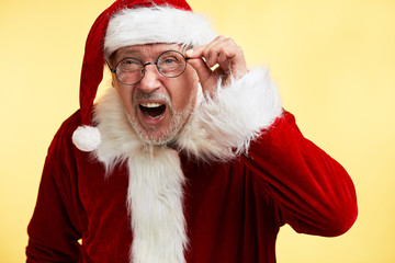 Indoor shot of mature Santa Claus, express great surprisment and amazement as hear unexpected news, stare at camera with bugged eyes, isolated over yellow background.
