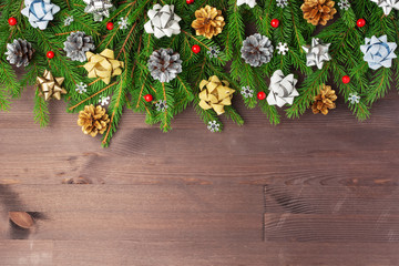 Spruce branches decorated with bows, red berries and snowflakes. The inscription Merry Christmas on a dark wooden background.