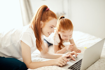 Cute little red-haired girl spend time with mom, browsing computer or shopping together. Young and technology concept