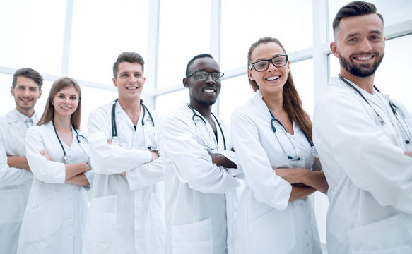 Group of smiling doctors with stethoscopes over white background