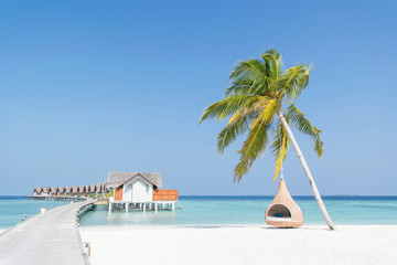 Stilt huts over sea against blue sky