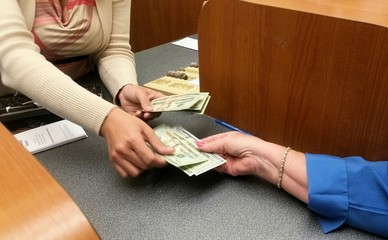 Cashier giving money to the customer in the bank