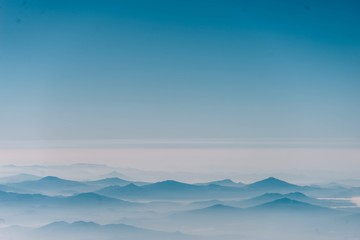 Aerial view of foggy mountains against blue sky