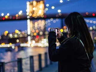Young woman taking picture in smartphone