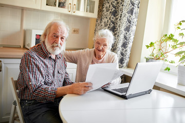 Mature couple sitting at kitchen table with laptop looking through financial papers, having little jam with the pension contributions.