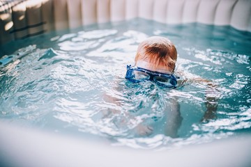 A boy wearing goggles while in a swimming pool