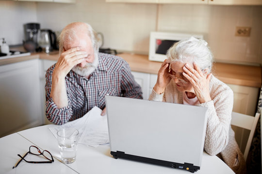 Frustrated mature caucasian couple sitting with laptop at home, aged retired man and woman sitting together and looking at papers, fail to understand, how they pay the bills.