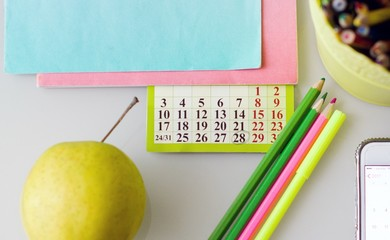 Close up of desk with book, calendar, pencils and green apple