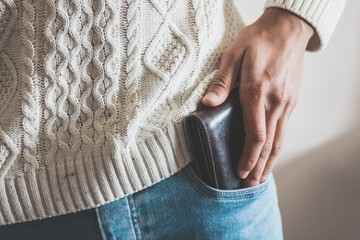 Midsection of a man putting a wallet in jeans pocket