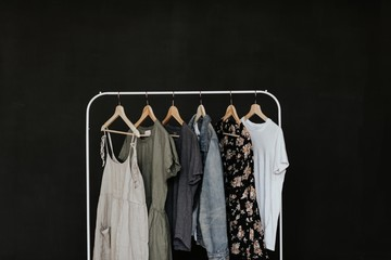 Clothes hanging on clothes rack against a black background