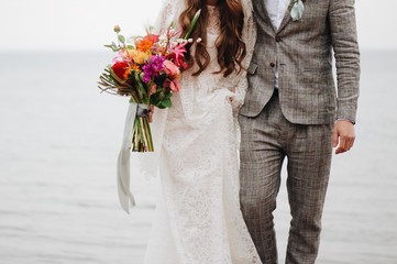 Mid section of bride and groom holding bouquet